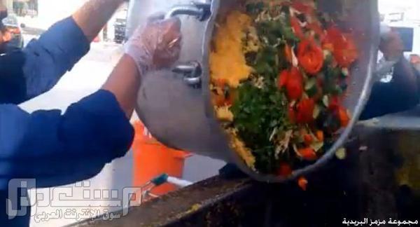 عمال نظافة يلقون كميات كبيرة من الطعام في حاوية نفايات أمام مبنى مرور شرق ا
